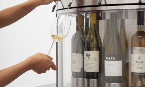 eno round enomatic wine dispenser system being used and showing wine pouring into a wineglass