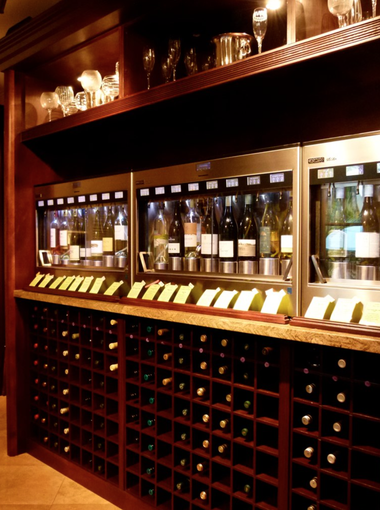 enoline elite wine dispenser system in a winebar with bottles underneath the enoline